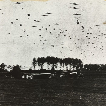 "Foto afsprong Poolse prachutisten bij Overasselt, 23 september 1944 boven gelande Amerikaanse Waco CG-4A zweefvliegtuigen. Tekst achterop: ""Luchtlanding Arnhem Sept. 1944""."