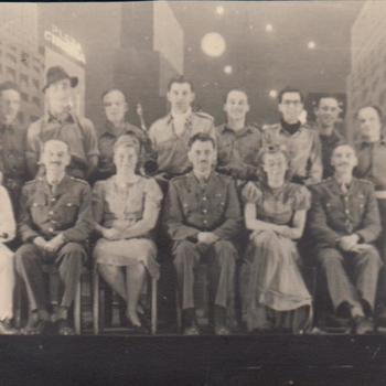 Foto van 19 mensen, 17 mannen en 2 vrouwen, op een podium voor een decor.