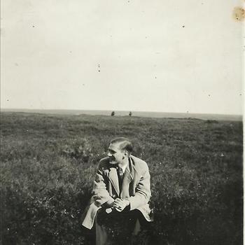 jongeman zittend in heideveld