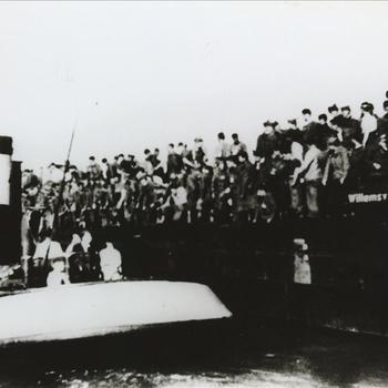 Vanuit een sleepboot wordt proviand aangereikt