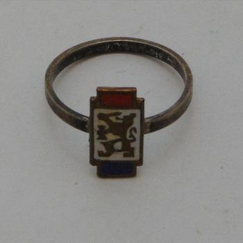 ring, met daarop de afbeelding van de Nederlandse Leeuw met op de achtergrond de kleuren van de Nederlandse Vlag ( rood, wit, blauw )