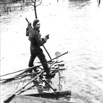 Canadese soldaat op vlot in overstroomt Leuth nabij Nijmegen, 1945
