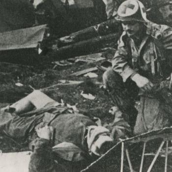 """Foto van Amerikaanse hospik bij gewonde na crash Waco GC-4A. Tekst achterop: """"Crashed Waco tijdens operatie """"Market Garden""""."""