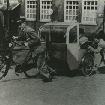 """Foto fietstaxi die aangeduwd wordt). Tekst achterop: """"fietstaxi in de oorlog""""."""