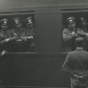 trein. Zes Duitse militairen (Heer) in uitgaans tenue hangen uit twee ramen