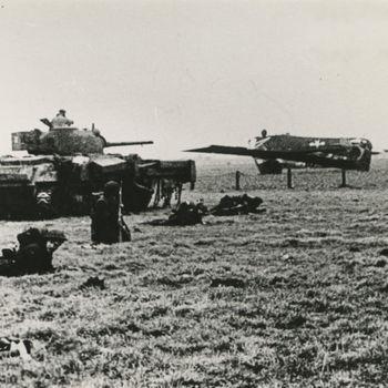 """Foto van op zijn kop liggende Amerikaans Waco CG-4A zweefvliegtuig met er voor Sherman Crab vlegeltank en Britse infanteristen. Tekst achterop: """"Groesbeek Febr. 1945 Klein Amerika""""."""