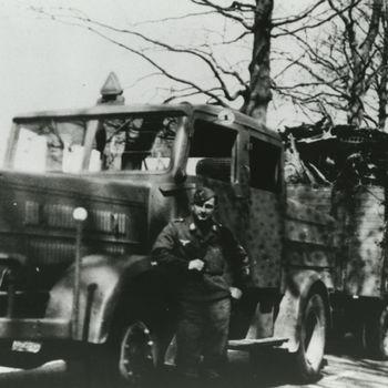 """Foto Duitse militair met vrachtwagen in camouflagekleuren. Tekst: """"Oldenbroek 1942""""."""