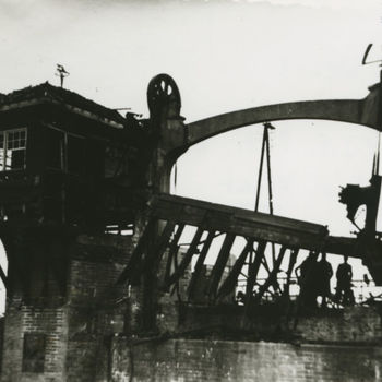 """Foto opgeblazen sluis over de Maas-Waal kanaal. Tekst achterop: """"Sluis Weurt mei 1940 foto F.J.F. Puts, Elst via J. v. Vliet""""."""