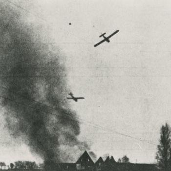 """Foto van twee Waco GC-4A zweefvliegtuigen bezig met landing. Gebouw staat in brand. Tekst achterop: """"Waco gliders in de landing tijdens operatie """"Market Garden""""."""