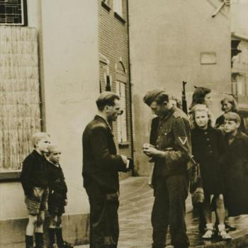 """Foto van Duitse militair die in straat persoonsbewijzen controleert. Tekst: """"Ronselen en razzia's in October 1944""""."""