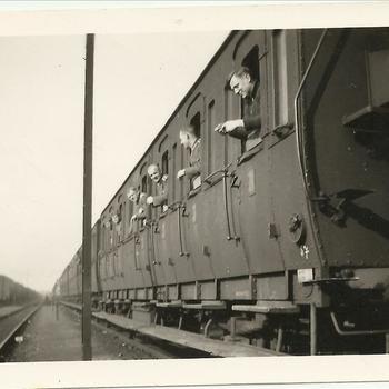 Duitse soldaten hangen door de open ramen van een trein