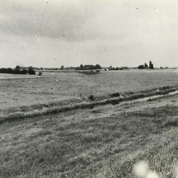 """Foto van weiland met sloot. Tekst achterop: """"Uiterwaarde Maas bij keent. Op deze plaats bevond zich het advanced airfield B-"""". Tekst er onder: """"Keent"""" bij Grave. In deze uiterwaarde van de Maas legden de Duitsers in augustus 1944 een hulpvliegveld aan. Na de Amerikaanse luchtlandingen in september 1944 werd dit de Engelse Advanced Base 82. Het vliegvled werd door duitse vliegtuigen verschillende malen aangevallen""""."""