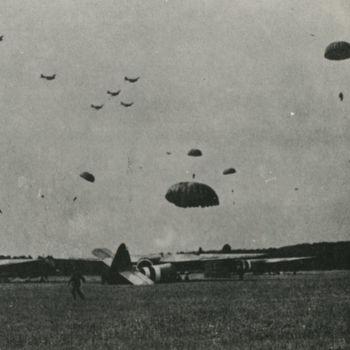 """Foto van dalende parachutisten op een landingszone van zweefvliegtuigen, Wolfheze, 17 september 1944. tekst achterop: """"Market Garden"""", 17-9-44 Horsa's en Airbornes A bridge too far blz 194"""".  Zelfde foto als 11.2.704"""