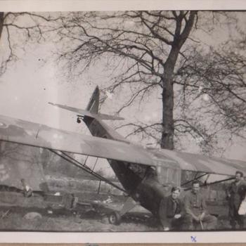 Foto van vier militairen bij een eenmotorig vliegtuig.