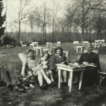 """twee echtparen in stoelen in tuin. Tekst achterop: """"± 1946"""""""