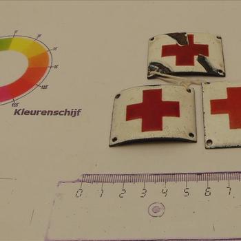 wit geëmailleerd plaatje met daarop het embleem van het Rode Kruis