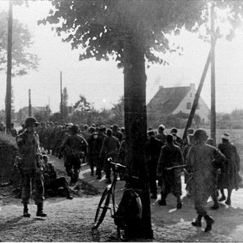 Foto van een collone gevangen Duitse soldaten, bewaakt door Amerikaanse soldaten