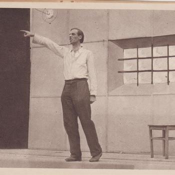 """Fotodruk van de scene waarin het gedicht """"de achttien """"Dooden"""" van Jan Campert wordt voorgedragen tijdens de uitvoering het toneelstuk """"Van Tyrannie tot Vrijheid"""" in 1945 te Terborg."""