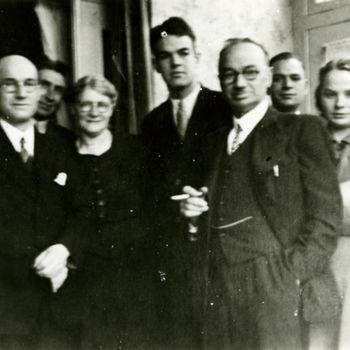 """Foto groep mannen en vrouwen. Een jonge man is een Amerikaanse vlieger in burger. Tekst achterop: """"Hurst bij familie F. Michels te Hintham. B-17 Eerde 20-10-1943""""."""