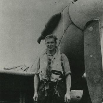 """Foto van jonge man in vliegerkledij voor neus Spitfire. Tekst achterop: """"P/O J.N. Thorne, DFC voor Mustang 122 Sqn. + 10-9-44 te Velp""""."""