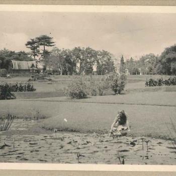 Lid Vrouwenkorps KNIL in de tuin van een palei in Nederlands-Indië
