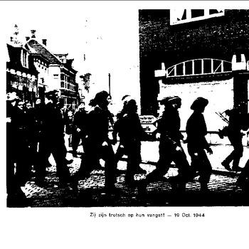 Foto (reproductie) van krijgsgevangen gemaakte Britse soldaten die door een straat van Den Bosch (waarschijnlijk) lopen. Zij worden begeleid door Duiste soldaten. De foto is gedateerd 19 oktober 1944.