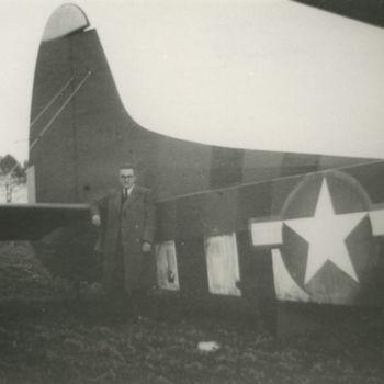 """Foto van  staartdeel van geland Waco CG-4A zweefvliegtuig. Ertegenaan leunt een Nederlandse burger. Tekst achterop: """"Hr. G. Peters uit Nijmegen bij Waco Overasselt""""."""