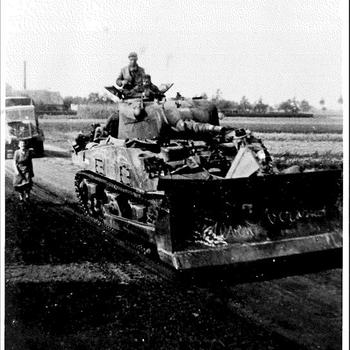 """Foto van een  Sherman tank met shovel en de Engelse bemanning. Op de shovel staat met krijt geschreven """"leven Overasselt"""". De foto is genoemen op de Kerkstraat (nu Schoonenbergese weg) te Overasselt."""
