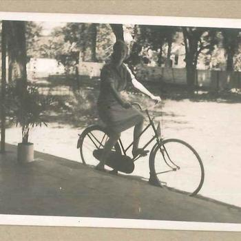 Lid Vrouwenkorps KNIL op een fiets in Nederlands-Indië