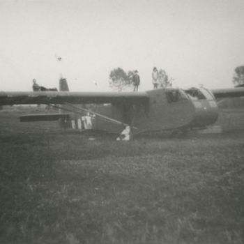 """Foto van weiland met geland Waco CG-4A zweefvliegtuig. Ruiten van cockpit zijn vernield. Tekst achterop: """"Waco Overasselt""""."""