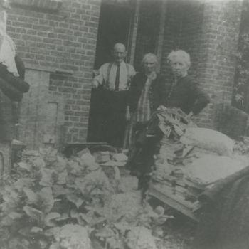 """Foto van drie burgers, twee vrouwen, een man voor huis. Man met overhemd aan. Voor dames stapel boeken. Tekst achterop: """"A'dam noord. Archief A. Karreman"""","""