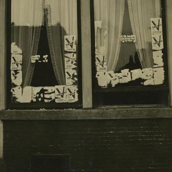 ruiten van woonhuis beplakt met V affiches