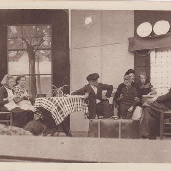 """Fotodruk van de scene voorstellende een interieur van een kamer met een achterhoeks gezin uit de uitvoering het toneelstuk """"Van Tyrannie tot Vrijheid"""" in 1945 te Terborg."""