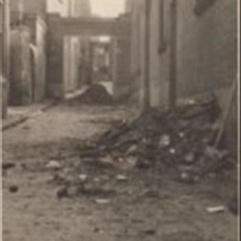 Foto van een beklinkerde straat in Nijmegen na het bombardement. Rechts brokken puin en verbrand hout.