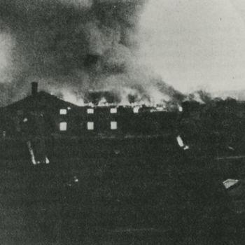 """Foto Willemskazerne in Arnhem die in brand staat. Tekst achterop: """"Arnhem 17-9-1944 De Willemskazerne in brand na aanval met Mosquito's""""."""
