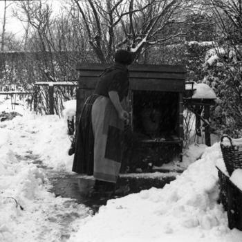 Vrouw in dracht bij afgesloten waterput, Hulshorst, 1946