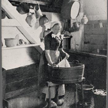 Vrouw in Veluwse streekdracht aan de was.