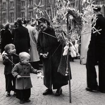 Speelgoedverkoopster en twee jongens met windmolentjes op een stok, Amsterdam, 1952