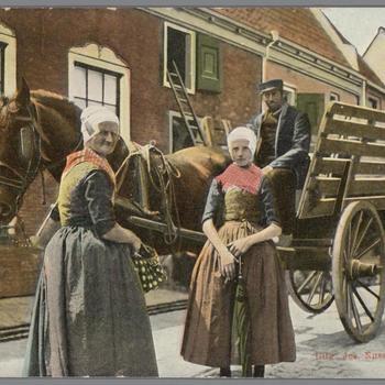 Twee vrouwen en een man in streekdracht van de Noordwest-Veluwe bij paard en wagen te Elburg