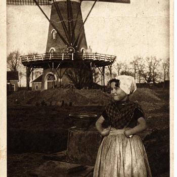 Meisje in Zuid-Bevelandse streekdracht bij molen, 1905-1922