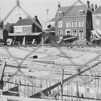 """Bouw schouwburg """"De Agnietenhof"""". Bij de bouw van schouwburg """"de Agnietenhof"""" hijst een kraan een betonstortbak over het bouwgedeelte. Geheel rechts boven het midden op de foto staat de betonwagen. De panden op de achtergrond zijn gelegen aan de Sint-Agnietenstraat"""