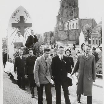 Optocht verzet. Op de Hucht trekt een bevrijdingsoptocht langs, georganiseerd door het verzet. Op de foto links een wagen van het kerkelijk verzet. Op de achtergrond rechts de ruine van de St. Maartenskerk