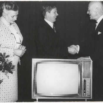 Afscheid Burgemeester Van Beekhoff (rechts), hij wordt gefeliciteerd, er staat een tv voor beide heren, mw. Van Beekhoff kijkt naar het apparaat.