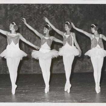 Vier danseressen in tutu op een rij, pose met alle vier rechterhand omhoog