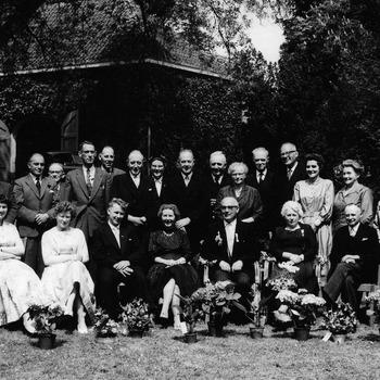 Een grote groep mensen bij de viering van het 40 jarig dienstjubileum van J.C. (Coba) Schellen als notarisklerk en G.A. (Gerrit) Ansing als boekhouder en administrateur bij het notariskantoor in Ammerzoden (Tot 1937 notaris H.C. de Jongh, daarna notaris G.E. Landweer). Achterste rij staand vlnr: 1. Jan Hen van Genderen, 2. H. van Keulen, 3. J.C. Quick, 4. Lies van Geffen, 5. Burgemeester C. v.d. Werken (Hedel), 6. Hennie Kaasjager, 7. Onbekend, 8. Koning, 9. C.J. Veldhuizen, 10. Van Veldhuizen, 11. Burgemeester Buysink (Zaltbommel), 12. Bax, 13. Prins (Landweer), 14. Notaris v.d. Akker (Kerkdriel), 15. Notaris G.A. Landweer, 16. Strookman, 17. Bloos (Schellen), 18. Zuster van G.C. Ansing, 19. Arie van Loon, 20. Garsky (Wagemans), 21. J.Th. Ansing, 22. J. Versteeg (Ansing), 23. Gemeentesecretaris Bertus Klop (Zaltbommel), 24. D. Ansing (van Leening). Voorste rij zittend vlnr: 1. J.J. Rijken (Schaaij), 2. Geertje Bax, 3. C. Schaaij (Mansing), 4. G.W. Ansing jr., 5. H.A. Wagemans (Mansing), 5. G.A. Ansing sr., 7. Coba Schellen, 8. Theo Schellen, 9. Blom (Wagemans), 10. P.W. van Maren (Ansing). G.A. Ansing bekleedde in de Bommlerwaard veel functies. Hij was onder andere ook gemeenteraadslid in zijn woonplaats Zaltbommel.