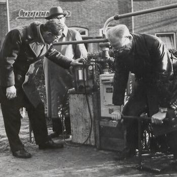 Mannen bezig met een pomp voor gebouw Coöperatie