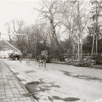 Tuin Ambtmanshuis. Met een hoogwerker wordt onderhoudswerk verricht aan de bomen in de tuin van het Ambtmanshuis. Op de voorgrond de 1e Achterstraat