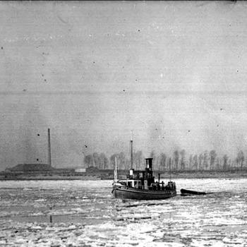 Boot (ijsbreker?) tussen de ijsschotsen op de Waal. Steenfabriek te Heesselt op de achtergrond.