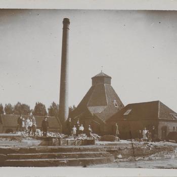Glasfabriek van de Firma van Hoytema. Te zien is een van de beide zogenaamde 'glashutten' waar de flessen voor de jenever vervaardigd werden. Op de achtergrond de bomenrij van de Veerweg.