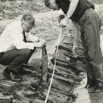 De opgraving van een Romeins schip te Kapel-Avezaath. Links op de foto professor Bogaers uit Nijmegen van de vakgroep Provinciaal Romeinse Archeologie, overleden in 1996. Hij is opgevolgd door Jan Kees Haalebos, overleden in 2001
